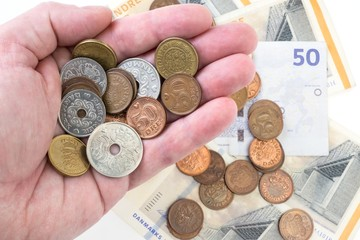 Hand with danish coins and money in the background