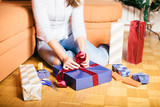 Young woman wrapping Christmas gifts in living room