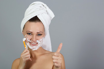 Girl shaving face and shows thumbs up at grey background