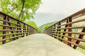 Pedestrian Bridge in a Park and Cloudy Sky