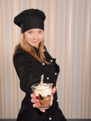 chef confectioner in black jacket, focus on tiramisu dessert