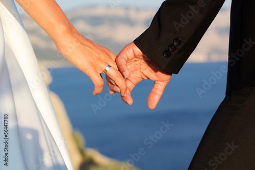 Wedding couple holding hands on sea background