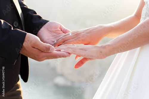 Wedding couple holding hands on sunset background