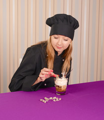 female chef conditer in black tunica decorating tiramisu dessert