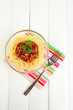 Italian spaghetti in glass bowl on wooden table