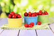 Cherry berries in bowls on wooden table on bright background