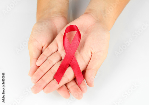 AIDS ribbon in hands isolated on white