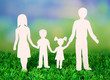 Family from paper on grass on bright background