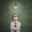 Young businessman under lit bulb in class