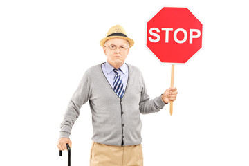 Angry mature gentleman holding a stop sign