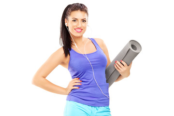 Female athlete listening music and holding a mat