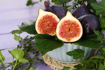Ripe figs in bowl in leaves on wooden table close-up