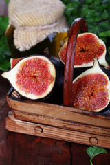 Ripe figs in basket on wooden table close-up