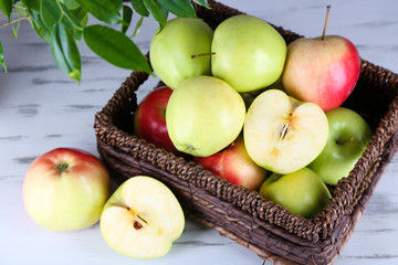 Juicy apples in basket on wooden table