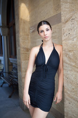 Young sexy woman with black dress posing outdoor
