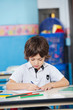 Boy With Sketch Pens Drawing In Kindergarten