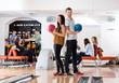 Young Man And Woman Holding Bowling Balls in Club