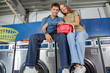 Couple With Clothes Basket Sitting On Washing Machine