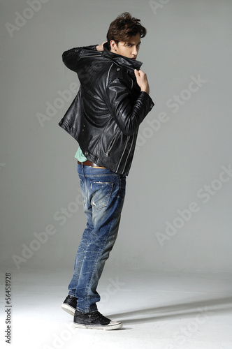 full length serious young man in leather jacket on gray