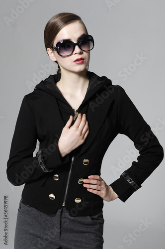 fashion model in sunglasses posing gray background