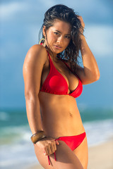 Woman in red swimsuit posing on the beach