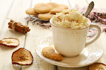 Cup of whipped cream coffee and apple cookies on wooden table