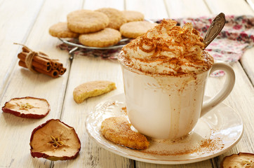 Cup of whipped cream coffee and crumbly cookies