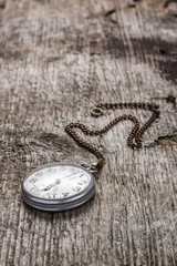 Old pocket watch at wood background