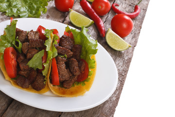 Mexican fast food: tacos stuffed with meat and vegetables