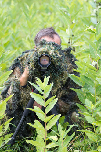 Photographer in ghillie suit in action