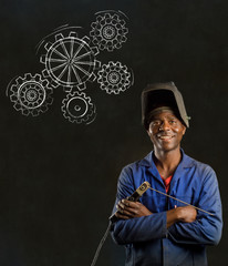 African man industrial worker with gears blackboard