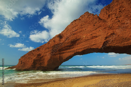 Amazing view of huge red cliffs with arch on the beach Legzira