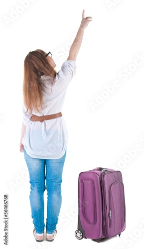 traveling young woman with  suitcas points at wall.
