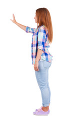 Young woman in jeans presses down on something.