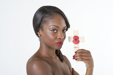 Black woman with a Remembrance cross and poppy