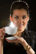 Portrait of beautiful woman posing in studio with cup of coffe