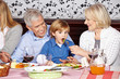 Großeltern füttern Kind beim Abendessen