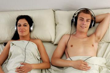 Pareja escuchando música en la cama.