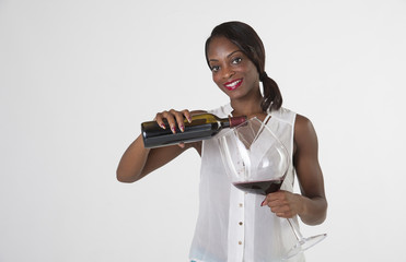 Black woman pouring red wine into very large glass