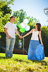 Adorable young couple holding bunch of balloons