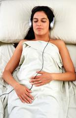 Mujer relajada escuchando música en cama.