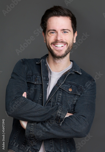 Happy young man smiling with arms crossed