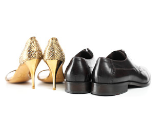 schwarzer Männerschuh und goldener Stöckelschuh