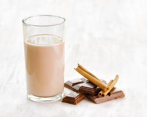 Chocolate milk with chocolate and cinnamon on white wooden table