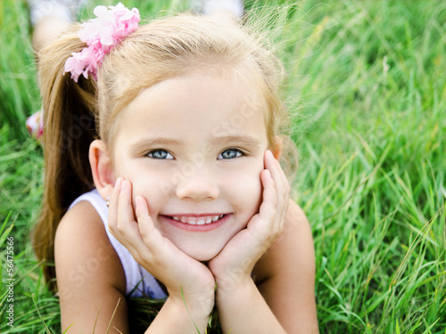 Cute smiling little girl lying in grass on the meadow