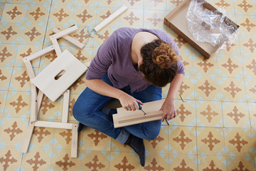 Young woman building piece of furniture