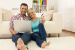 Happy loving couple sitting on the floor and using laptop