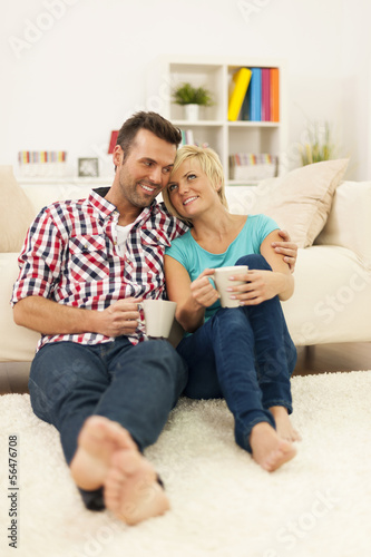 Happy couple sitting on the floor and drinking coffee