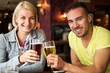 Beautiful couple enjoying beer in a pub