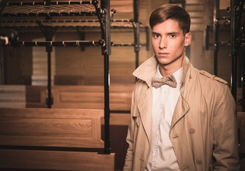 Handsome young man in coat inside vintage train